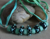 Turquoise and ink blue floral lampwork necklace on a hand-dyed silk ribbon by Claire Dunn SRA SRJAD