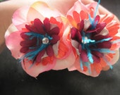 Black glitter headband with pink, orange, gray, maroon flowers with blue feathers and rhinestones.
