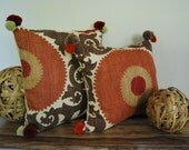 Earth tone suzani pillows with matching pompoms