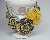 Rosette Bib Necklace in gray, yellow and ivory with an adjustable chain.