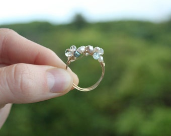 Gold wire wrap ring with freshwater pearls, glass, and blue topaz.
