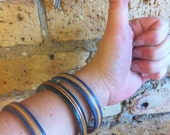 Recycled Girl and Almost skateboards, S/M wrist bangles. Dark blue, turquoise, orange, and natural colors.
