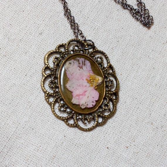 pressed flower necklace resin soft pink larkspur set in resin. romantic oval filigree pendant for summer. prairie.