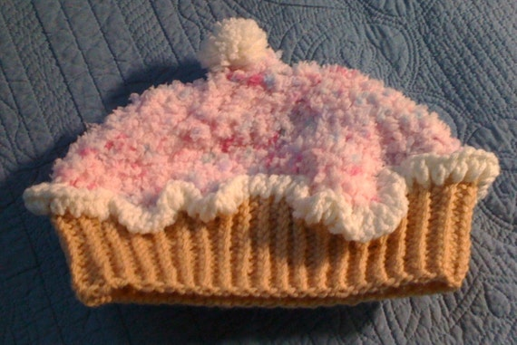 knit vanilla cupcake hat topped with pink confetti icing/frosting and a pom pom/marshmallow
