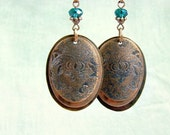 Copper earrings with flower pattern.