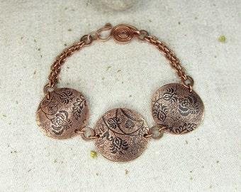 Copper bracelet with flower pattern.