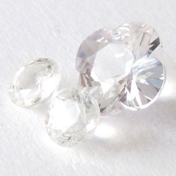 Genuine white sapphire, Africa, 2 rounds 3.2 mm and 1 flower-shape 5.9 mm, Lot (3) of 1.16 carat