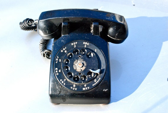 Vintage black rotary telephone, retro photo, landline, black and white, retro home decor.