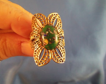 Large gold tone flower ring with green stone and colorful specks