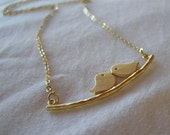 Matte gold bird on branch necklace