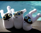Three little Beegus sitting in the sun, baby sock toys every single one.