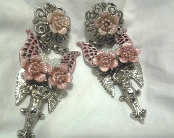 Vintage Angel  connected to a mauve color set of wings, silver tone on bottom, flowers and beaded heart, and chains .
