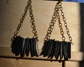 Dangling black coconut shell on antique bronze chain cross cable