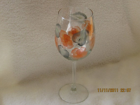 Wine glass with orange flowers and green leaves hand painted