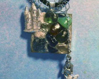 "SandyCastle awaits Mermaid.She dangles freely by tiny chain. Sand path through sea glass leads to the castle.20""Black velvet necklace  21.00"