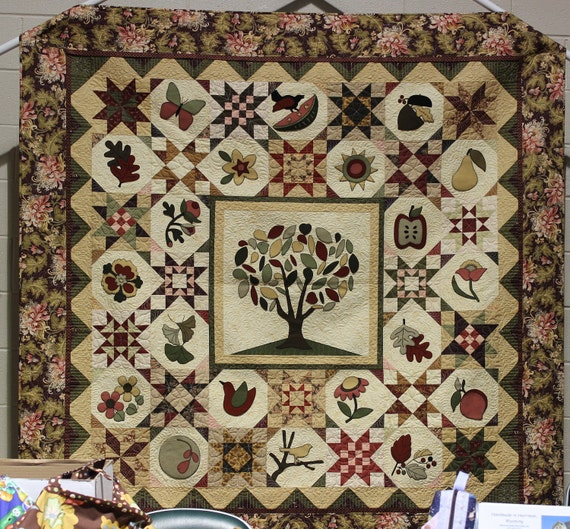 Tree of Life handmade quilt with felted wool applique and pieced stars in cotton fabrics.
