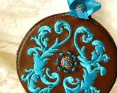 Keychain in brown leather, round shape with blue embroidery , silver filigree pearl . Handmade leather keychain - hand embroidered