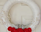 white yarn wrapped holiday wreath with red felt flowers and pearl berries