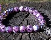 Purple beaded bracelet with silver charm