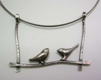 Two Silver Birds Perched on a Wire