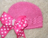 Pink crocheted hat with pink and white polka dot bow attached