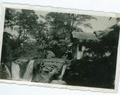 Waterfall and building in tropical forest, vintage photography