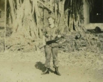 Vintage photograph: WWII Armed soldier posing with a huge tree