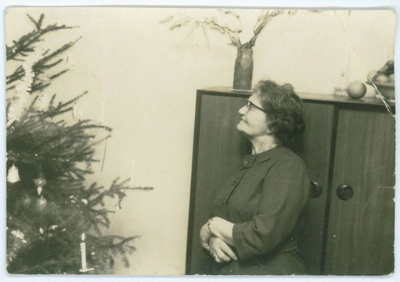 Old lady looking at her christmas tree, vintage photograph