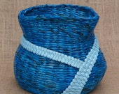 Irregularly misshapen blue storage basket hand made from recycled newspaper (paper wicker)