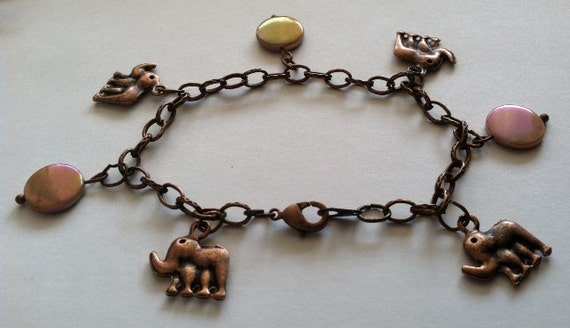 Antique copper charm bracelet with lucky elephant charms and shimmering peach colored flat shell pearls.