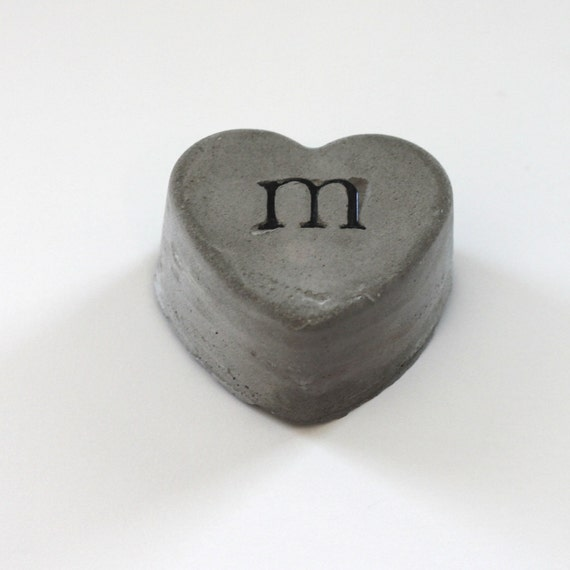 cement heart embedded with black letter M