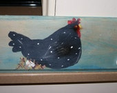 chicken wall hanging with two different pegs for hanging items .