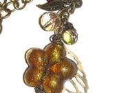 Antiqued bronze pendant necklace with bronze leaf and amber glass flower
