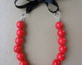 Bright red ceramic beaded necklace, ties up with a pretty black ribbon
