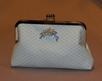 Ivory suede clutch with blue russian net overlay and pearl brooch