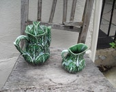Coffee pot and creamer made of majolica,  in  the shape of a   green  cale