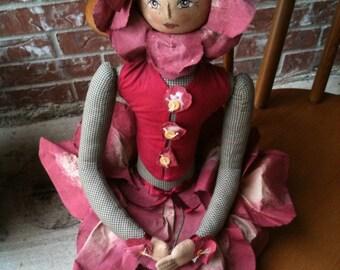 Hand painted face folk art ragdoll with fabric flower petal skirt holding a stem