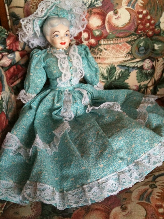 The red lipped lady porcelin hand painted doll with matching lace turquoise bonnet & dress.
