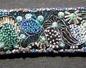Beaded felt cuff bracelet in greens, blues and silver.