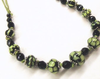 Green and black lampwork necklace on green raw silk cord