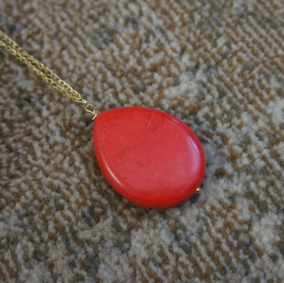 long gold tone chain with red stone pendant