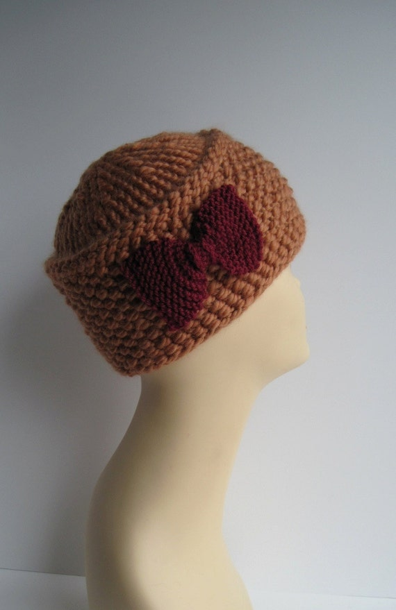 Golden pillbox knit hat with red knit bow