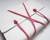medium white leather journal with pink wrap cord