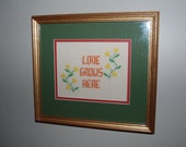 This is a framed vintage needlepoint with a love and nature theme for the home