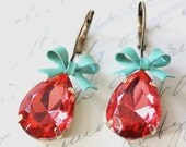 Bright coral colored orange/pink faceted glass rhinestones with bright turquoise blue bows. brass leverback earrings.