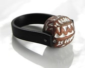Black rubber band ring with big brown white acrylic bead.