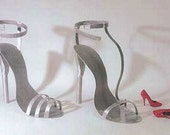 Large metal high heel shoe sculptures in aluminum by sculptor Bruce Gray