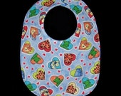 Baby Bib Animal Friends features a blue background  with colorful hearts, each framing  animals: lions, tigers, giraffes, bears, BB002