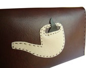 brown and cream purse with pipe