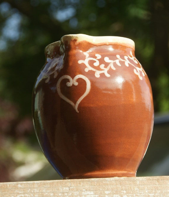 Pitcher with heart and vines in burnt orange glaze on stoneware hand